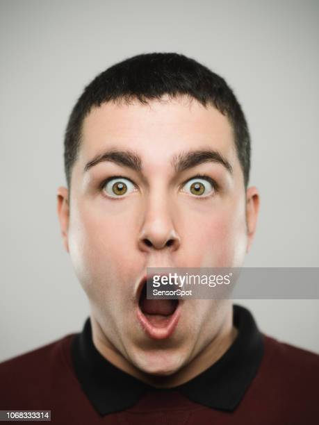 portrait of a surprised young caucassian man looking at camera. - surprise stock pictures, royalty-free photos & images