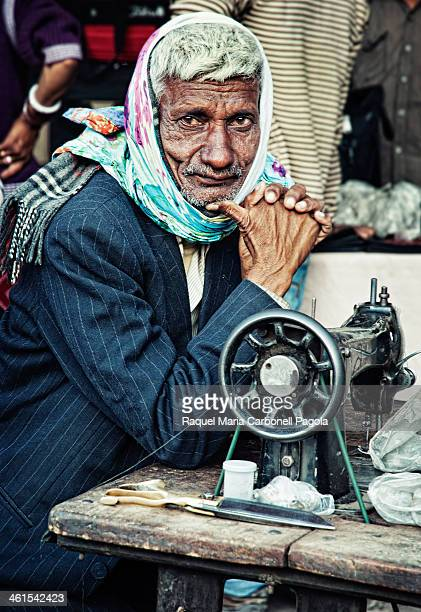 Portrait of a tailor sitting at his sewing table