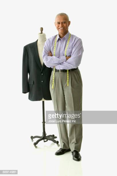 Portrait of a tailor standing beside a mannequin