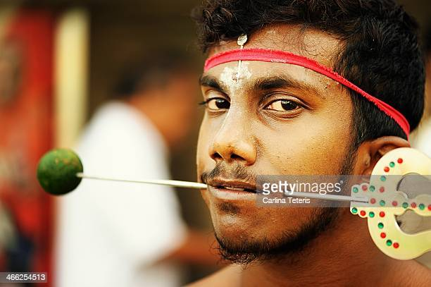 CONTENT] Portrait of a Tamil Singaporean man with a large bar pierced through both cheeks with a lime covering the tip during Taipusam festival...