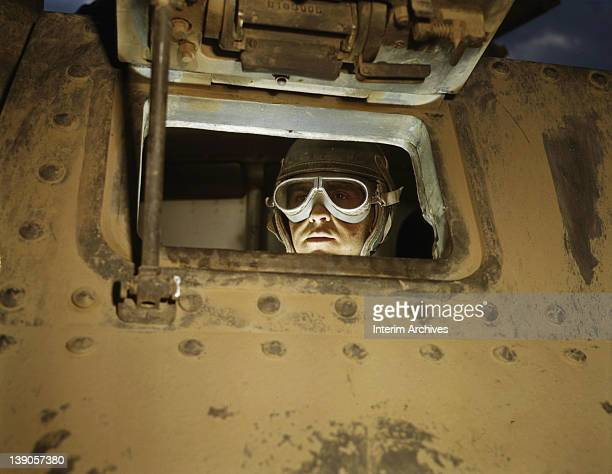 Portrait of a tank driver peeking through the M3 tank's window in Fort Knox Kentucky June 1942