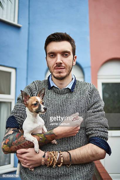 A portrait of a tattoo enthusiast and his dog