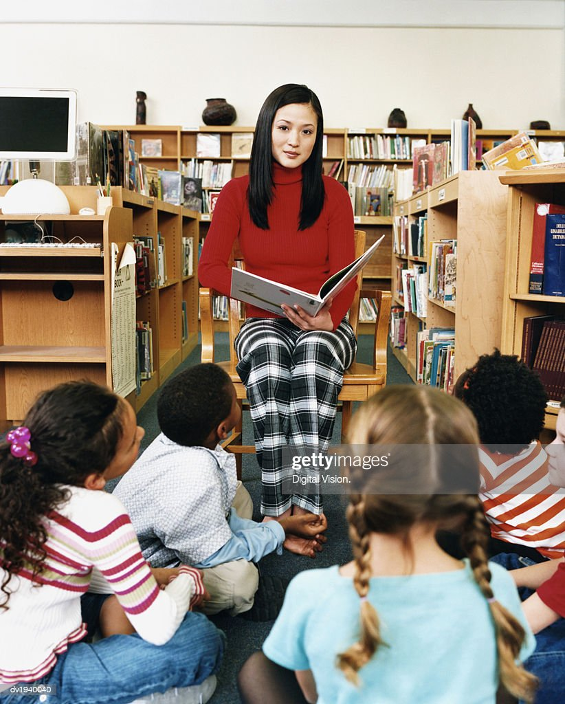 Portrait of a Teacher Reading a Story Book to a Small Group of Children in a Library : Stock Photo