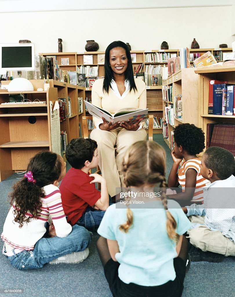 Portrait of a Teacher Reading a Story Book to Primary School Students in a Library : Stock Photo
