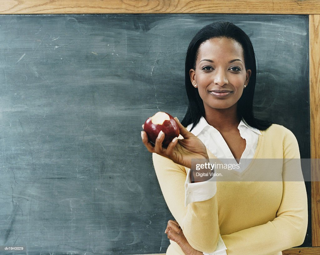 Portrait of a Teacher Standing in Front of a Blackboard Eating an Apple : Stock Photo