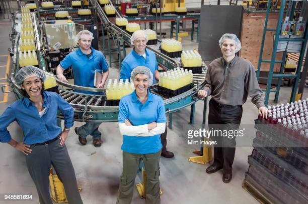 Portrait of a team of male and female workers and male management person standing next to a production line conveyor belt of lemon flavored water in a bottling plant.
