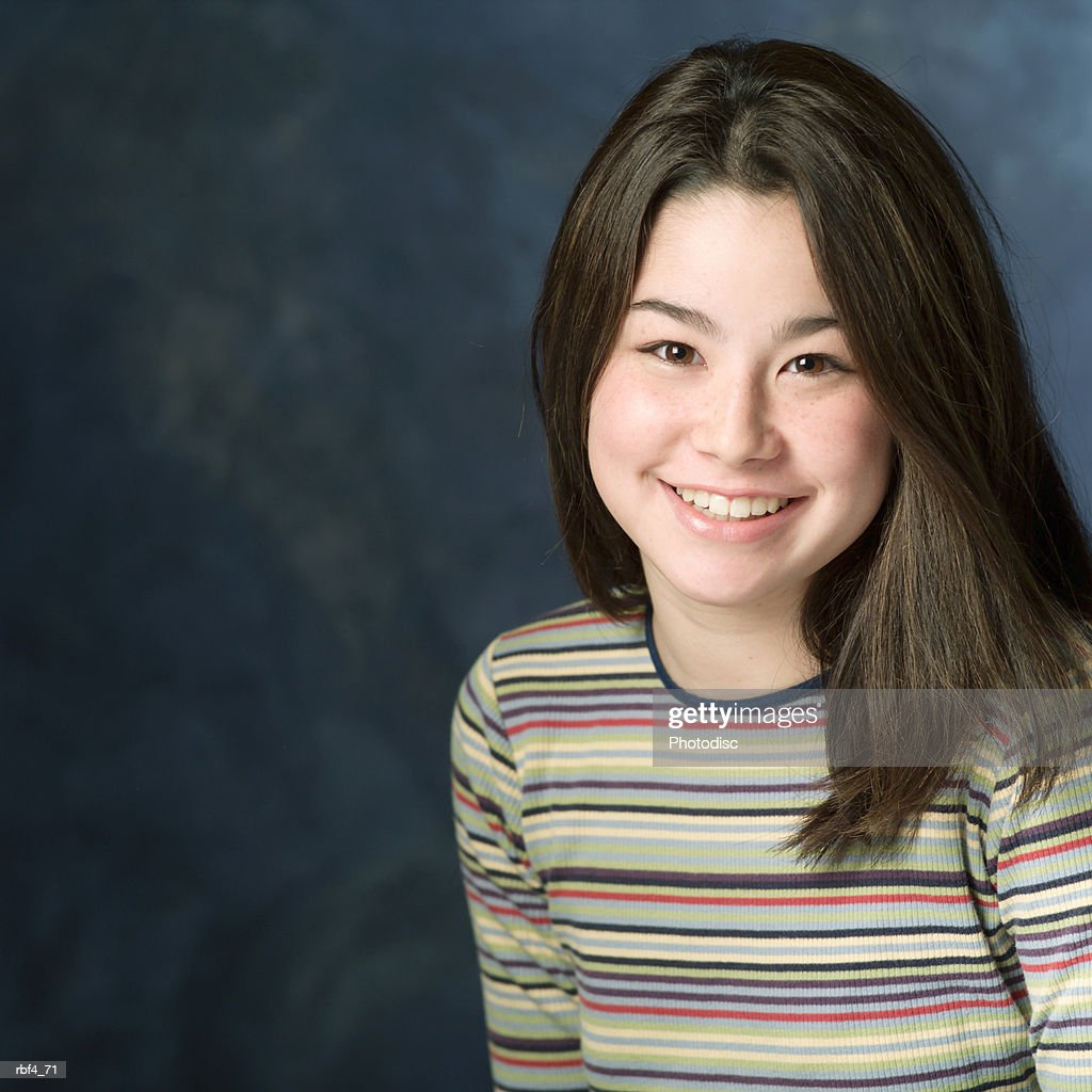 portrait of a teenage asian girl in a multi colored sweater as she smiles at the camera : Stock Photo