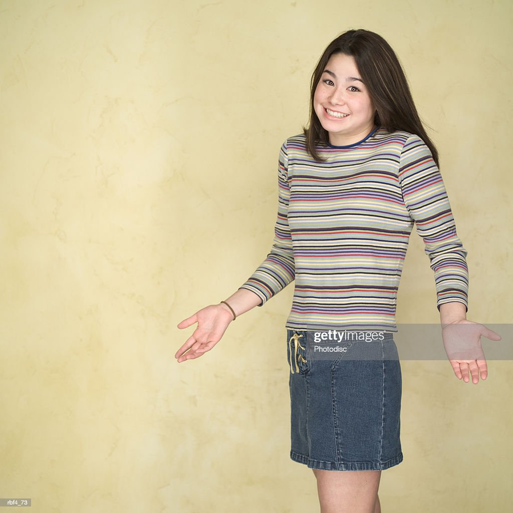 portrait of a teenage asian girl in a multi colored sweater as she shrugs her shoulders and gestures with her hands : Stockfoto
