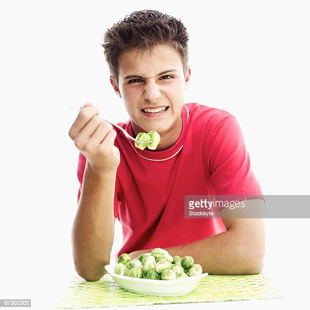 Portrait of a teenage boy (15-17) frowning at Brussels sprouts on a fork