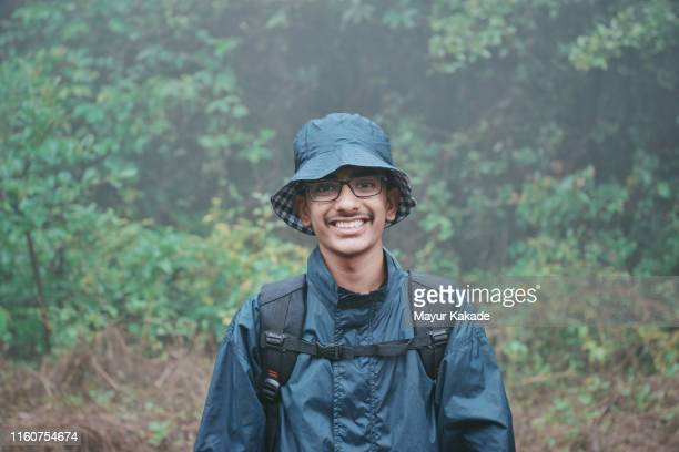 portrait of a teenage boy hiking on the rainy day - チューリップ帽 ストックフォトと画像