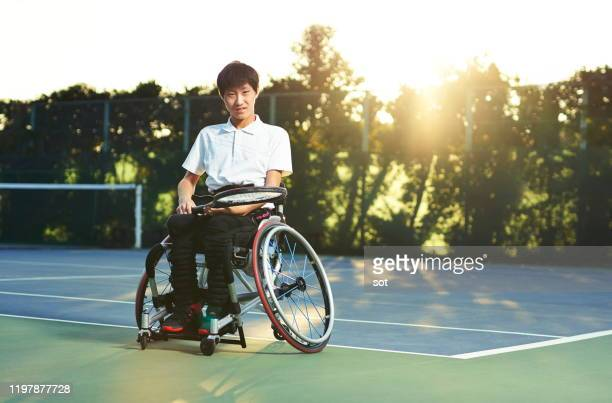portrait of a teenage boy in a wheelchair on a tennis court - 車いすテニス ストックフォトと画像
