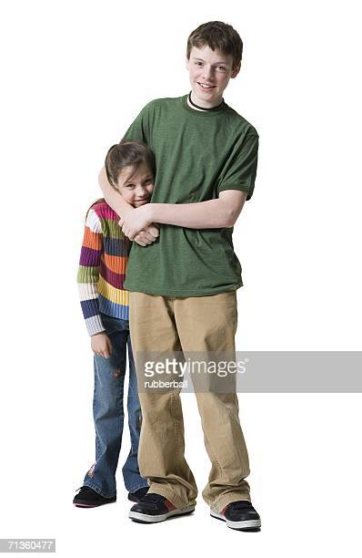 Portrait of a teenage boy picking on his sister