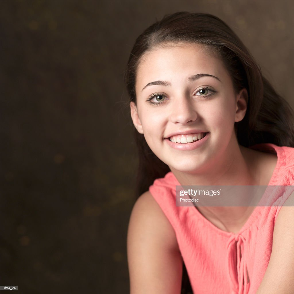 portrait of a teenage ethnic female in a pink sleeveless shirt as she smiles into the camera : Stockfoto