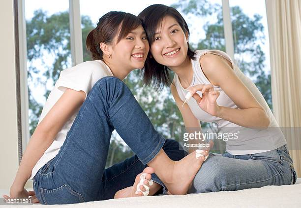portrait of a teenage girl applying nail polish on another teenage girl's toenails - teen girls toes stock photos and pictures