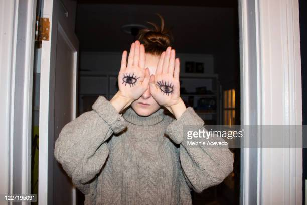 portrait of a teenage girl covering her eyes with her hands which have drawings of eyes on them. shot from the chest up. indoors. - obscured face stock pictures, royalty-free photos & images