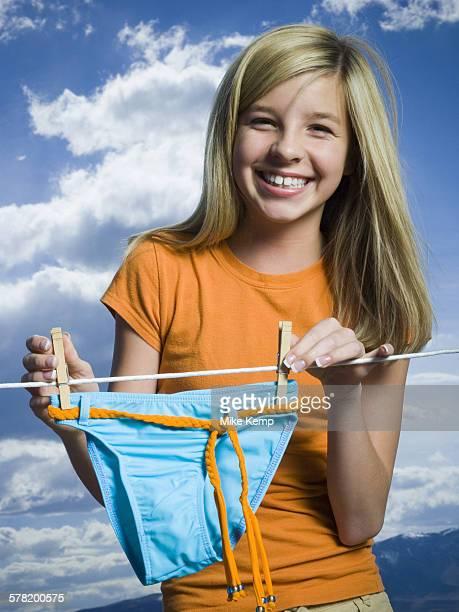Portrait of a teenage girl drying a bikini bottom on a clothesline
