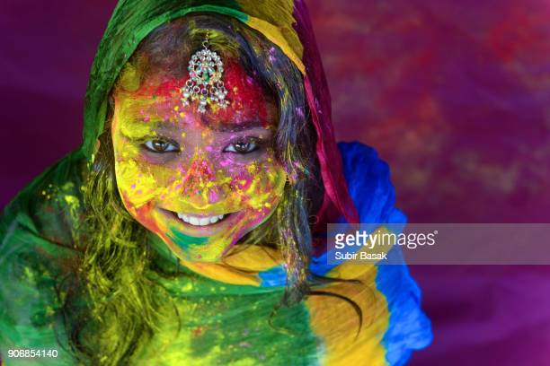 portrait of a teenage girl enjoying holi festival. - holi stock pictures, royalty-free photos & images
