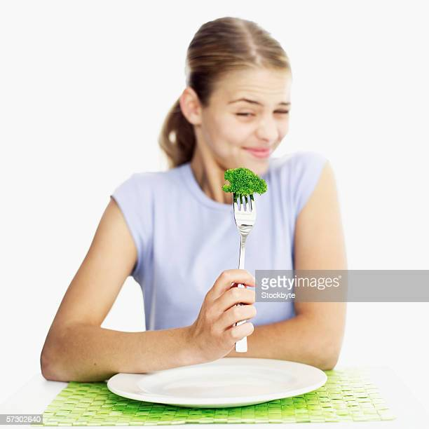 Portrait of a teenage girl (15-17) frowning at a piece of broccoli on a fork