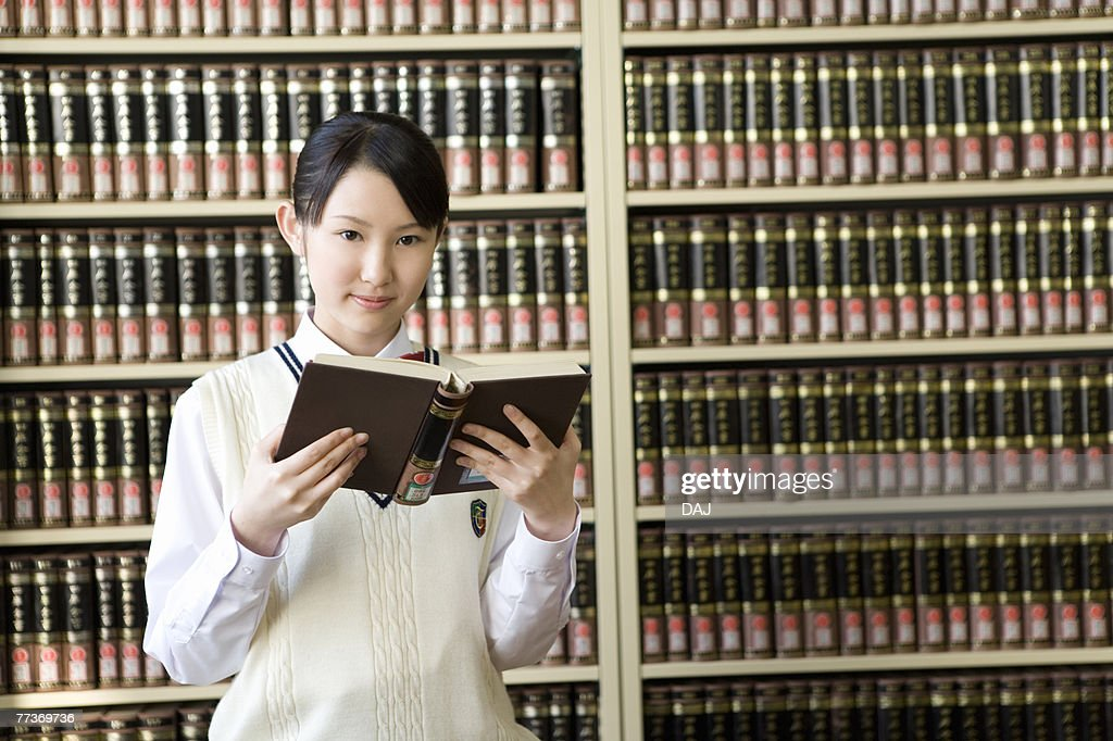 Portrait of a teenage girl holding a book in front of bookcase, smiling and looking at camera : Photo
