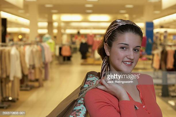 Portrait of a teenage girl holding a shopping bag in a shopping mall