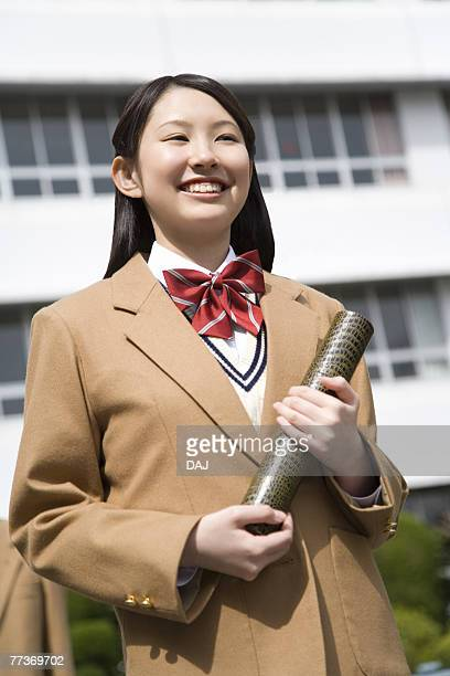 Portrait of a teenage girl holding diploma, smiling