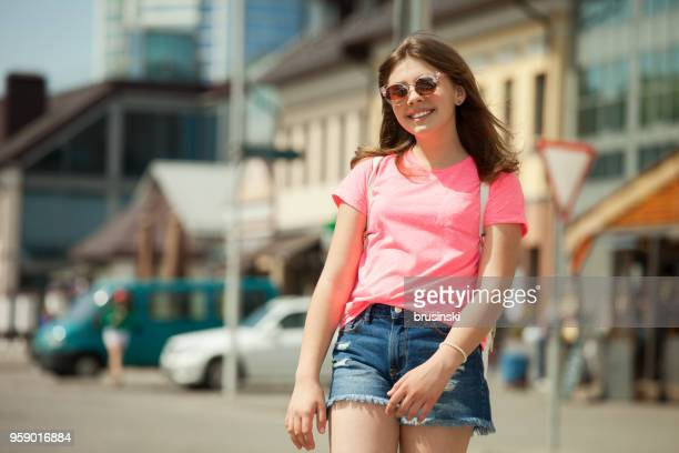 portrait of a teenage girl in a pink t-shirt for a walk in the city