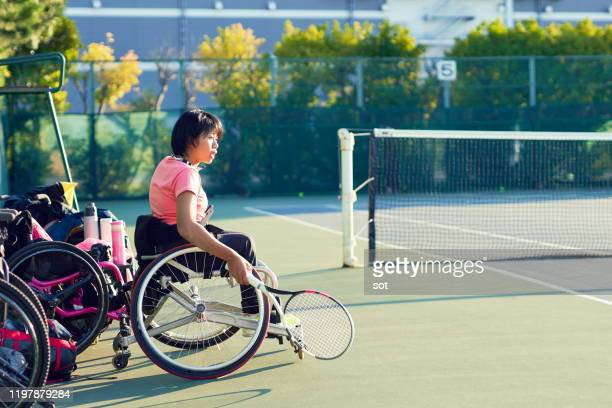 portrait of a teenage girl in a wheelchair looking at tennis court - 車いすテニス ストックフォトと画像
