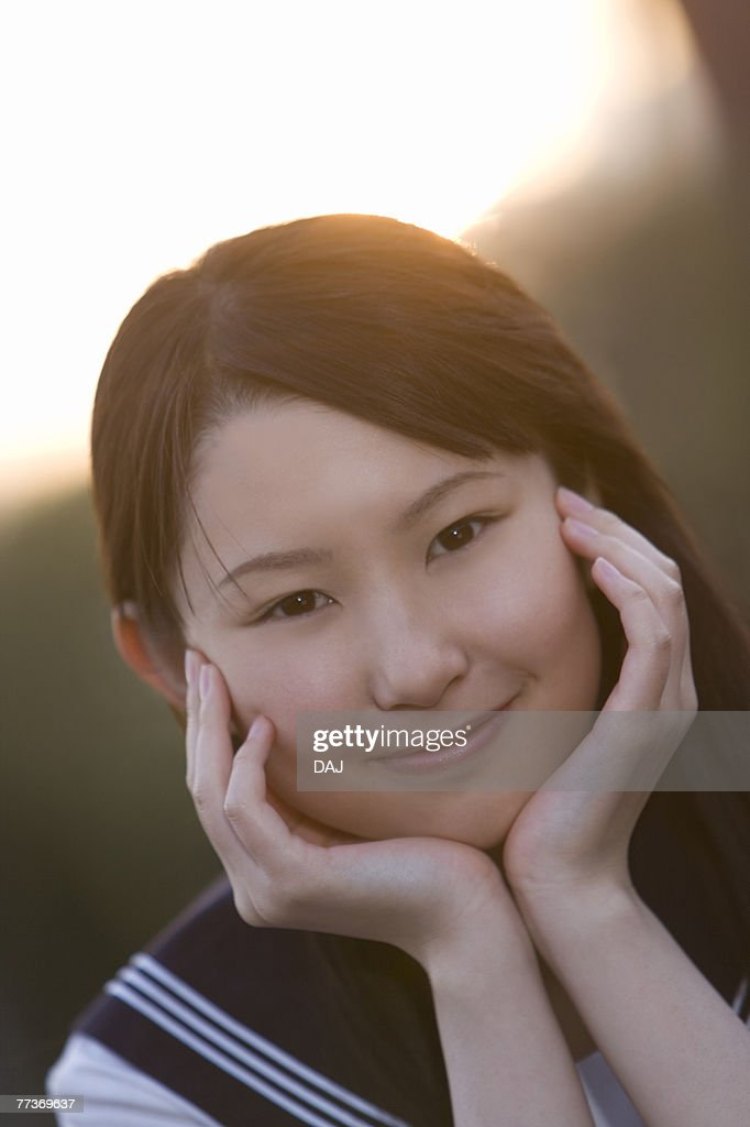 Portrait of a teenage girl sitting and resting chin in hands in schoolyard, smiling and looking at camera : Photo
