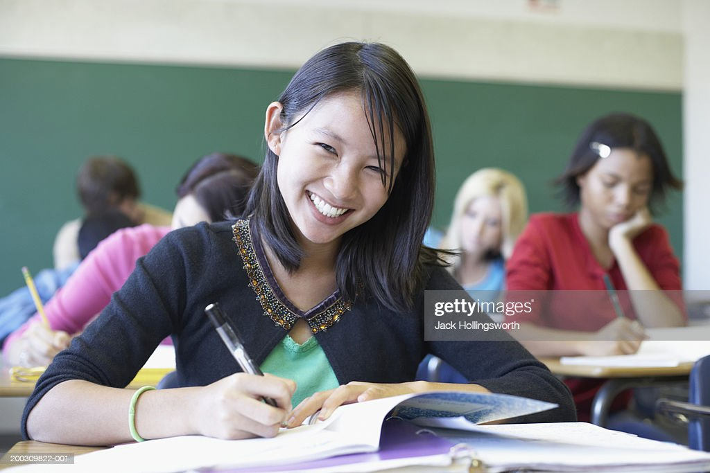 Portrait of a teenage girl sitting in a classroom : Stock Photo