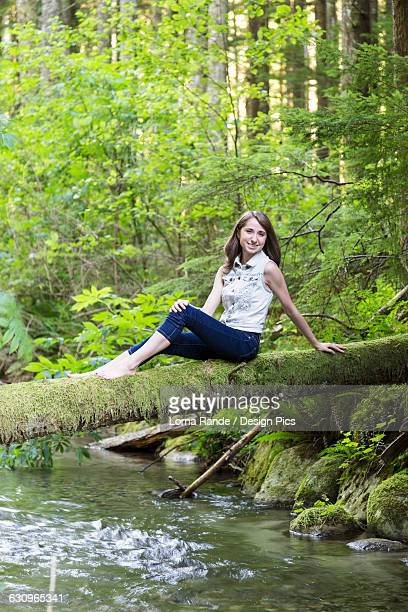 Portrait of a teenage girl sitting on a moss covered log over a stream