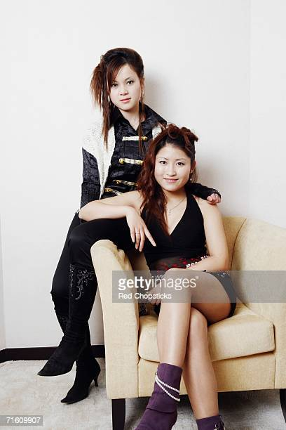 Portrait of a teenage girl sitting on an armchair with her friend