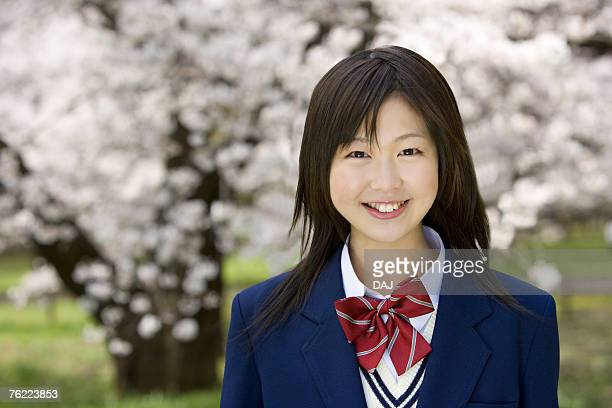 Portrait of a teenage girl smiling and looking at camera, cherry trees in background, front view, Japan