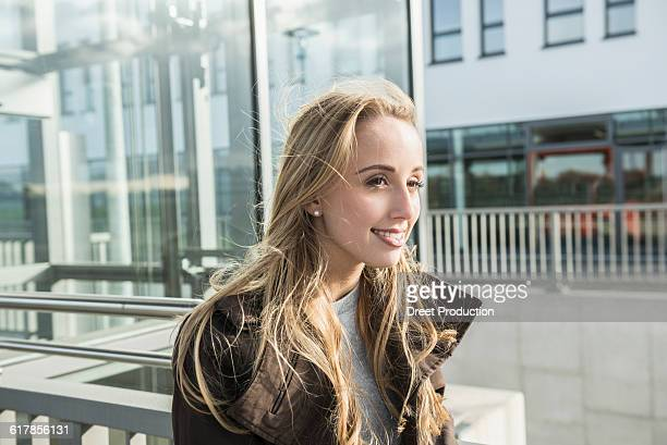'Portrait of a teenage girl smiling in a city street, Munich, Bavaria, Germany'