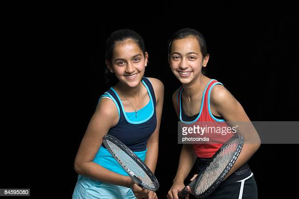 Portrait of a teenage girl smiling with her sister and holding badminton rackets