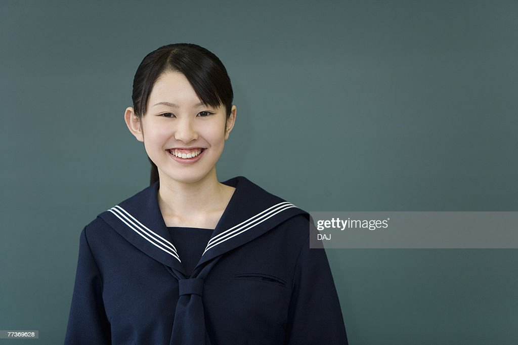 Portrait of a teenage girl standing in front of blackboard, smiling and looking at camera, green background : Stock Photo