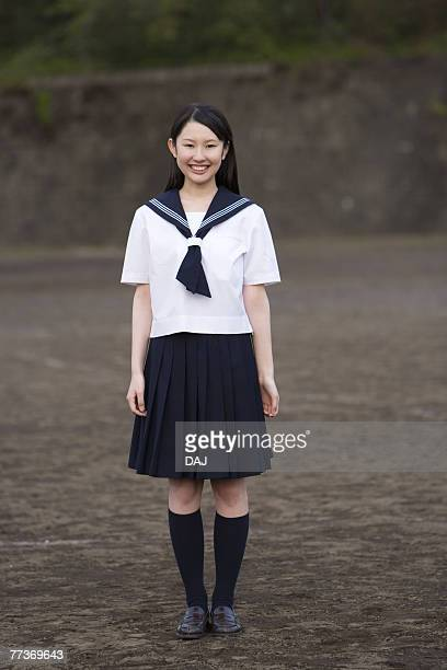 portrait of a teenage girl standing in schoolyard, smiling and looking at camera - female high school student stock photos and pictures
