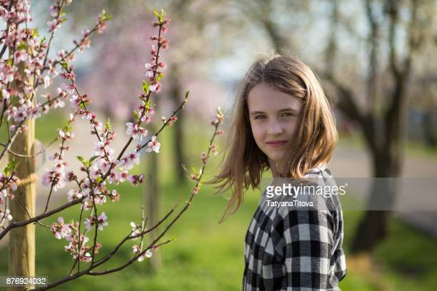 portrait of a teenage girl with a blossoming almond tree