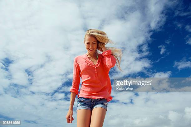 portrait of a teenage girl with long blond hair against a blue sky and cloud; kauai, hawaii, united states of america - low angle view photos et images de collection