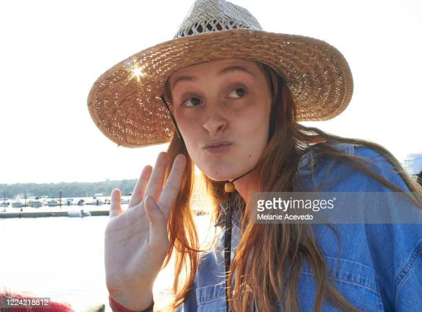 portrait of a teenage girl with red hair at the beach wearing a big straw hat, waving, and making a funny face at someone off camera. there is a back lit light flare on the photo, and golden light. - redhead stock pictures, royalty-free photos & images