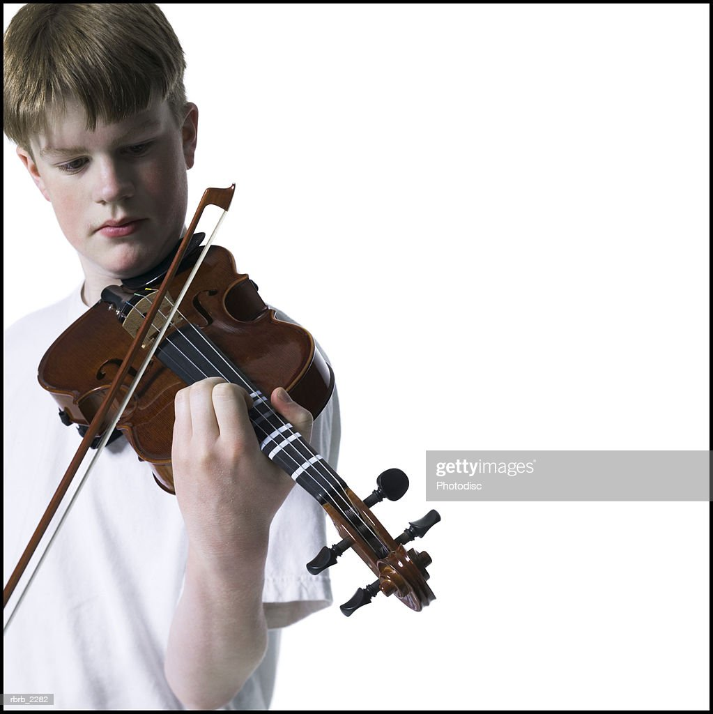 portrait of a teenage male as he holds up and practices his violin : Foto de stock