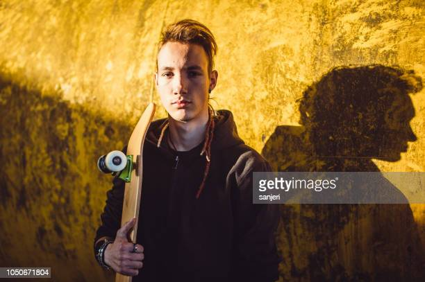 portrait of a teenager boy holding a skateboard - one teenage boy only stock pictures, royalty-free photos & images
