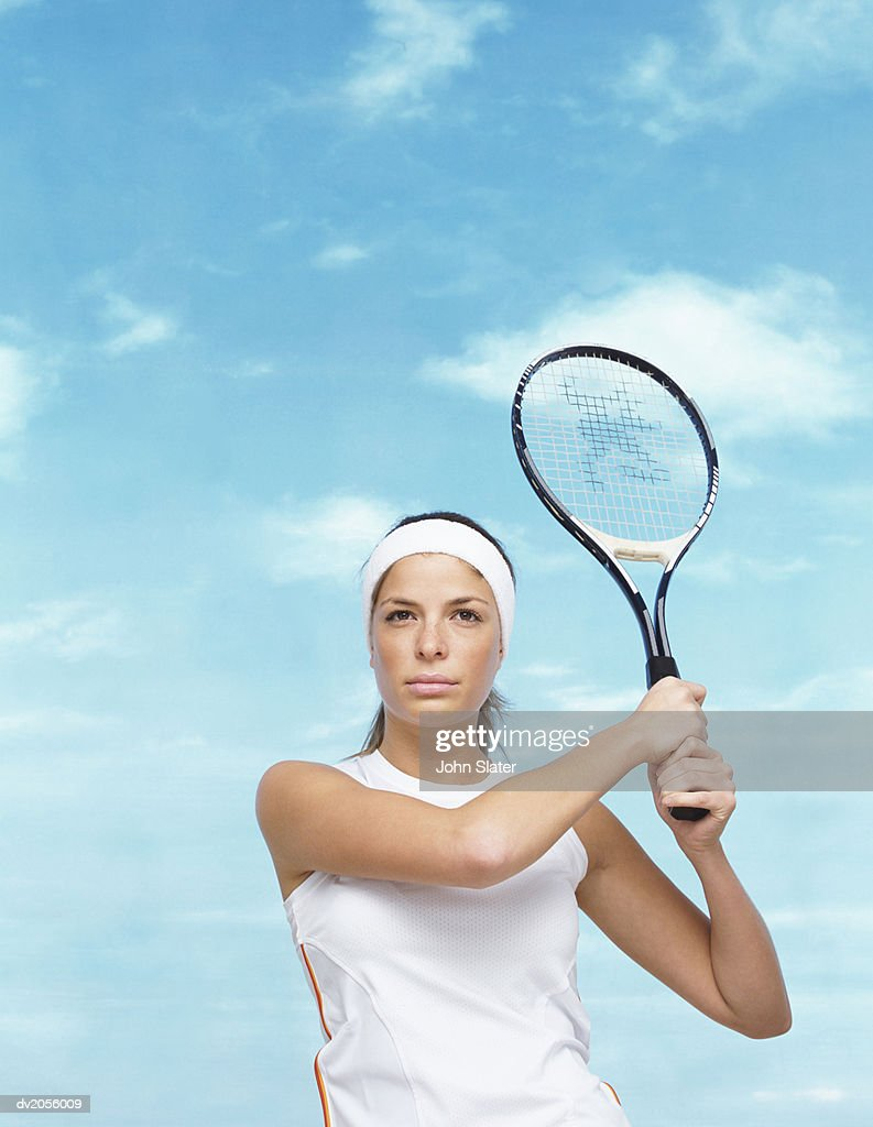 Portrait of a Tennis Player Holding Her Racket in the Air : Stock Photo