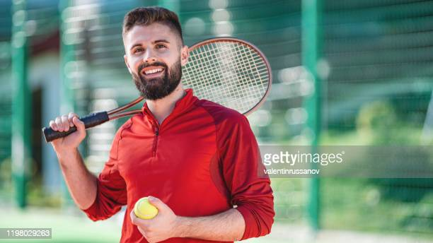 portrait of a tennis player looking at camera smiling while holding his tennis racket - tennis player stock pictures, royalty-free photos & images