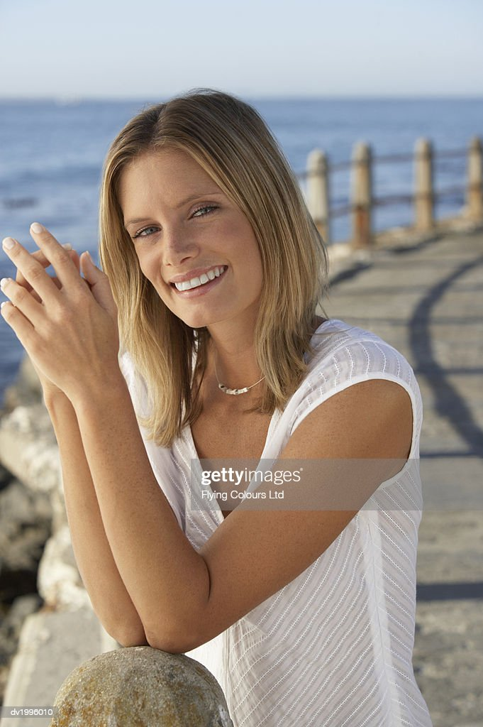 Portrait of a Thirtysomething Woman Standing on a Coastal Promenade : Stock Photo
