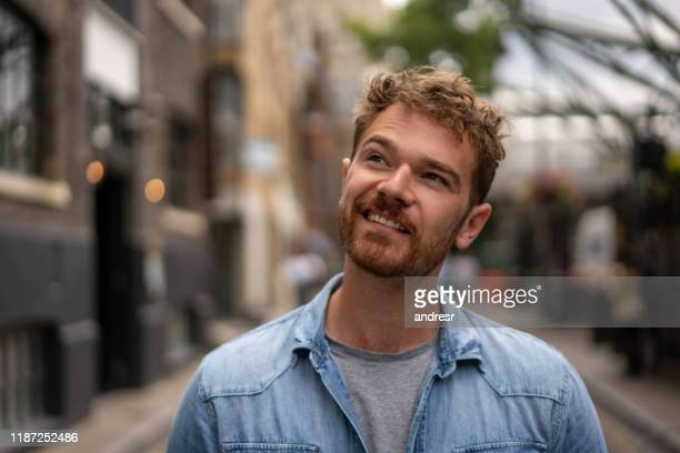 portrait of a thoughtful man smiling on the street - caucasian ethnicity stock pictures, royalty-free photos & images