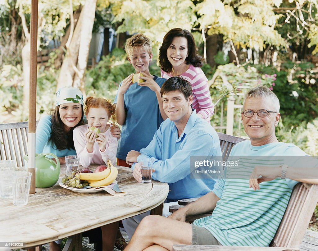 Portrait of a Three Generational Family Sitting at a Garden Table : Stock Photo