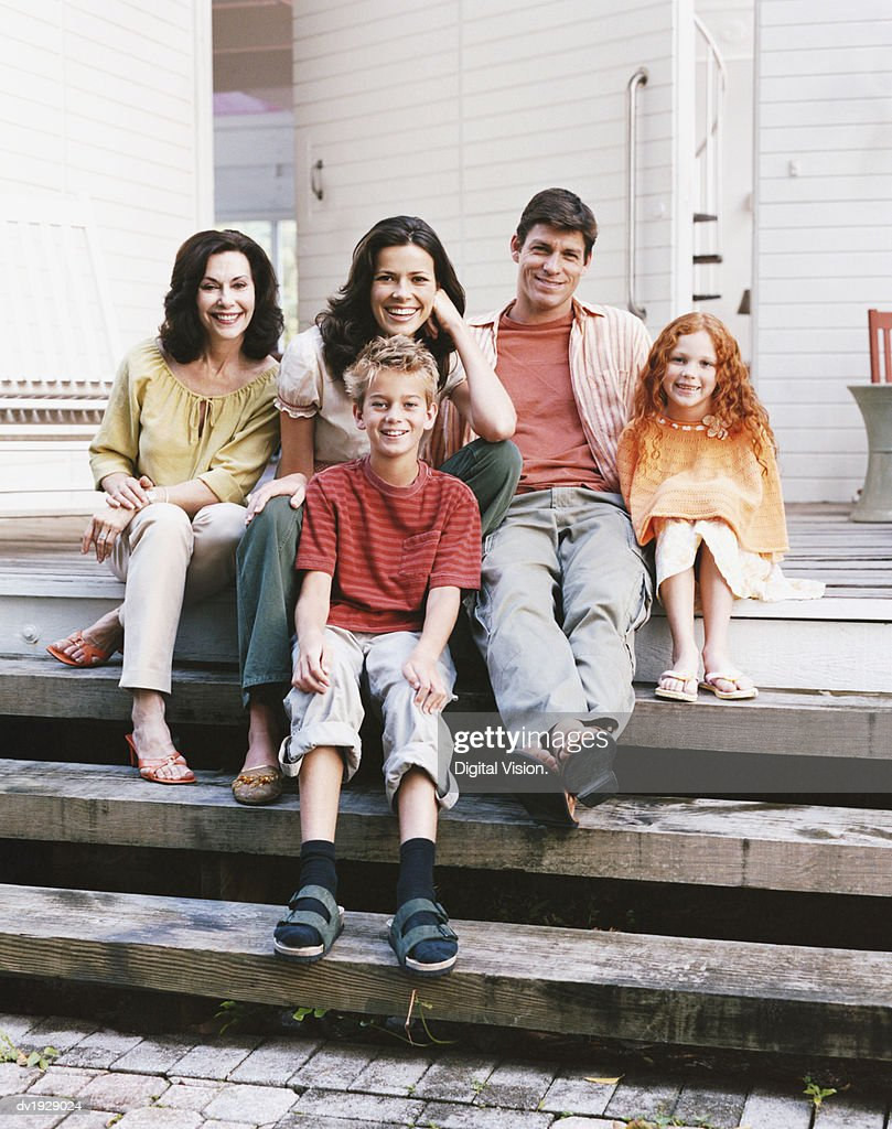 Portrait of a Three Generational Family Sitting on the Steps to Their House : Stock Photo