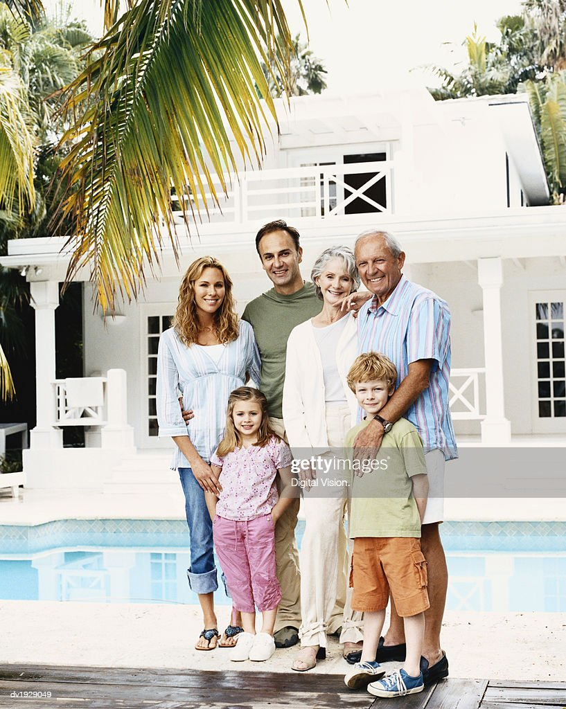 Portrait of a Three Generational Family With a Young Boy and Girl Standing by a Seimming Pool : Stock Photo