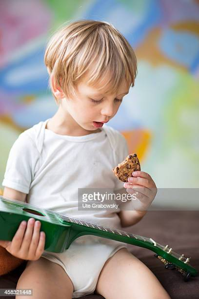 Portrait of a threeyearold boy with a cookie and a children's guitar on August 05 in Sankt Augustin Germany Photo by Ute Grabowsky/Photothek via...