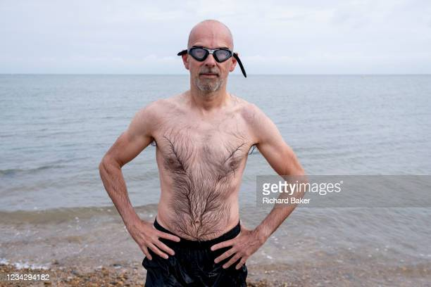Portrait of a tired but fulfilled male sea swimmer who has just left the tidal waters after his swim several metres away from the beach on the Thames...